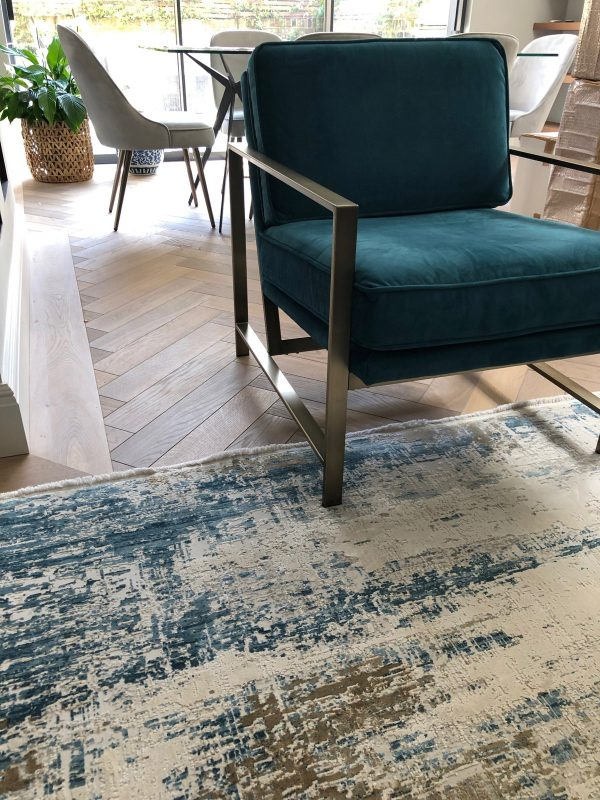 blue abstract rug with velvet chair