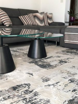 modern rugu with cream and grey design in room with glass coffee table