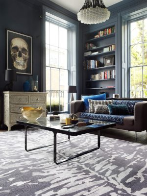 grey and silver silk leaf design rug in room with dark blue walls