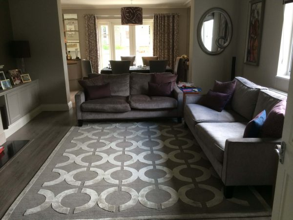 geometic rug with circles with brown sofa