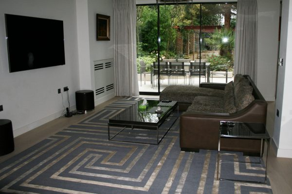 geometric modern rug with silk in room with brown leather sofa