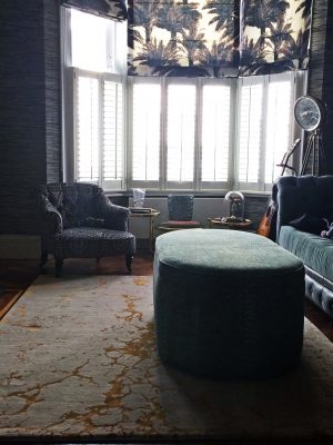 wool and silk luxury rug in living room with green velvet sofa dark and moody