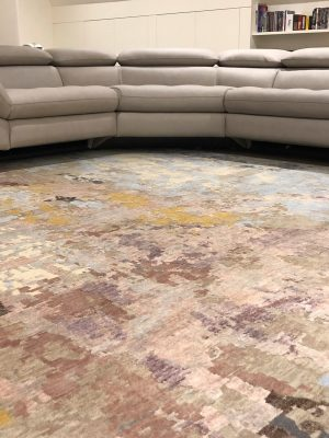 multi-coloured pastel abstract rug with grey corner sofa