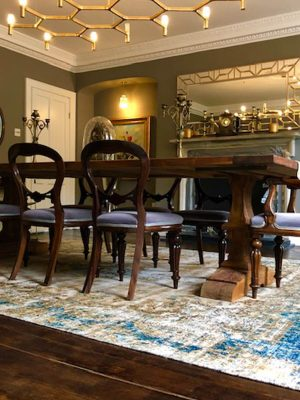 blue and gold distressed vintage rug in dining room with dark wood table