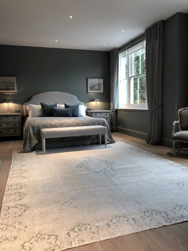 faded vintage Persian rug in modern bedroom