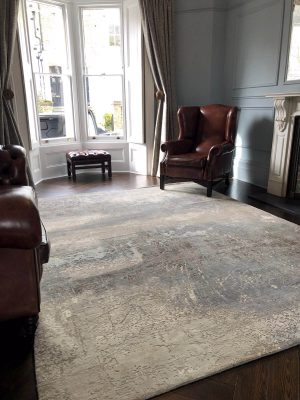 grey abstract rug with wool and silk and leather armchair