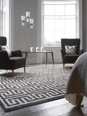 geometric monochrome rug with greek key design in room with black armchairs