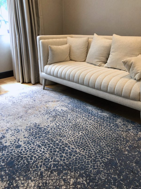 blue luxury rug in living room with cream sofa