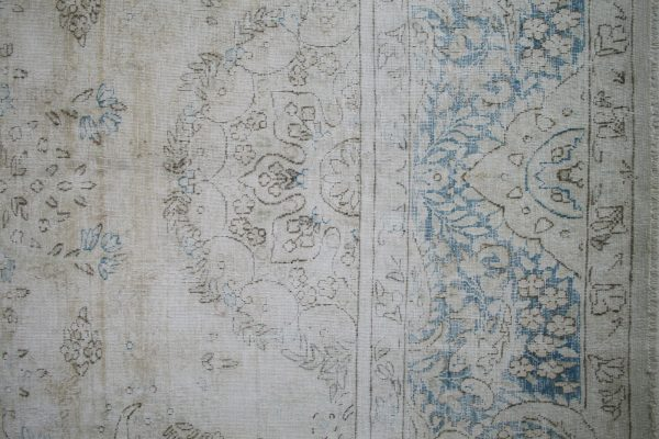 blue and beige faded rug close up