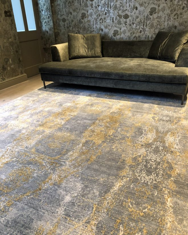 luxury gold silk rug in living room with velvet sofa